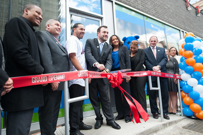 Center with scissors, Ryan Fogarty, WellCare's vice president, New York and Connecticut, cuts the ribbon to WellCare's newest Welcome Center in Manhattan's Washington Heights. To Fogarty's left is New York Mets catcher Rene Rivera, to Fogarty's right is Jeanette Gonzalez, WellCare's senior director of provider relations. WellCare Welcome Centers are neighborhood health information, education and activity centers.