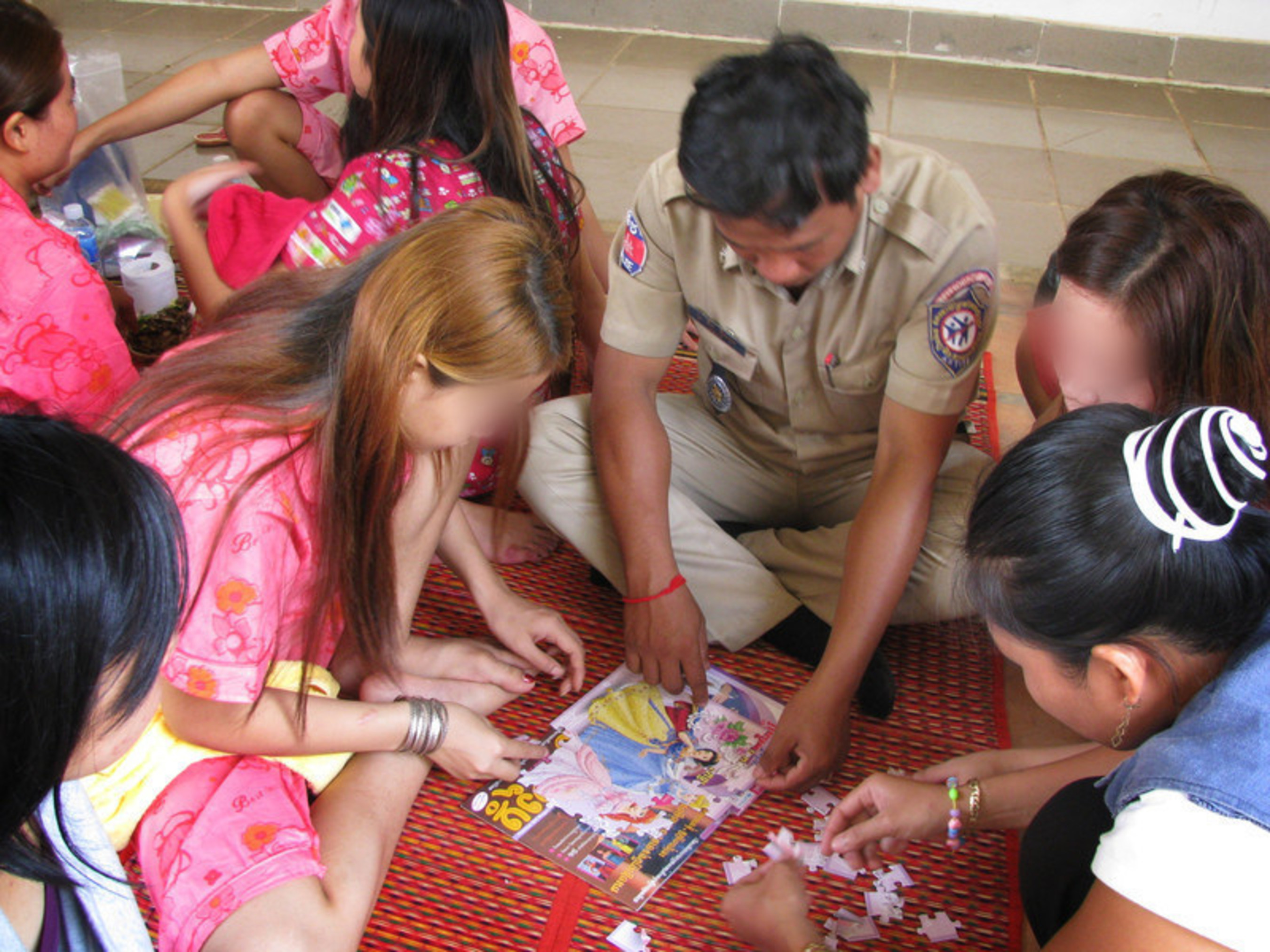 A Cambodian police officer helps trafficking survivors piece together a princess puzzle.  Since the early 2000s, Cambodia has made enormous progress in combating the commercial sexual exploitation of children.