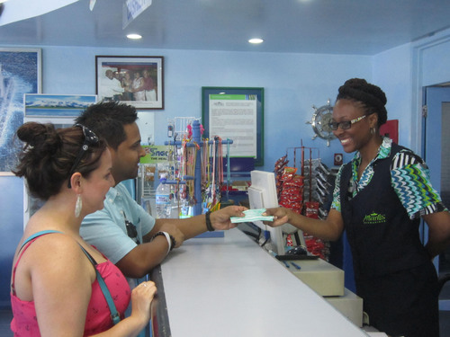 Pictured above from left, Natalie Escobar and Alex Abibula from the United States redeeming their vouchers for a FREE Atlantis Submarine tour.  (PRNewsFoto/Barbados Tourism Authority)