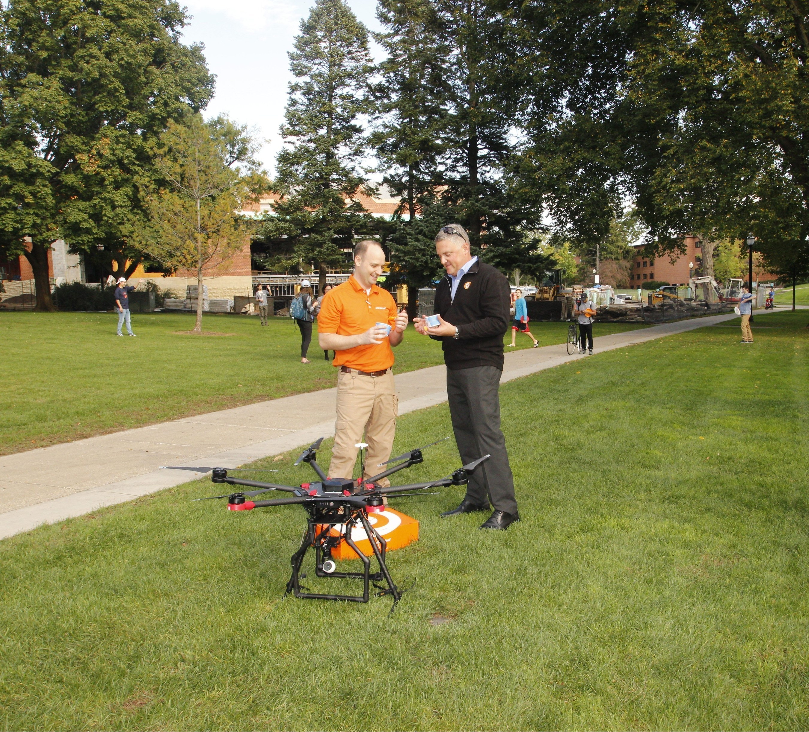 Orange Leaf President, Geoff Goodman, and franchise store owner, Jeremy Latchaw, celebrate the landing of the brand's delivery of frozen yogurt by drone.