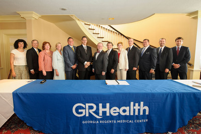 Nadia Butler, Tom Kirkland, Khry Reinseth, Deborah DiSanzo, Steve Laczynski, David S. Hefner, Dr. James Rawson, Matt Bierbaum, Susan James, Greg Damron, Shawn Vincent, Greg Nesbitt and Brian Lynde pose for a photo following the signing of a contract announcing an alliance with the Georgia Regents Medical Center at the The Pinnacle Club on Thursday, June 27, 2013, in Augusta, Georgia. The agreement, worth approximately 300 million, is the largest of its kind for Philips and the a first of its kind healthcare delivery model in the United States. (Paul Abell/AP Images for Philips Healthcare).
