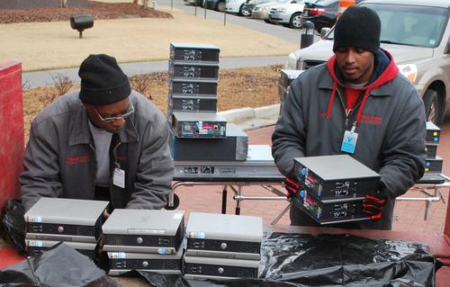 Clinton Public School District maintenance staffers Teddy Hines (left) and Derrick Jenkins load computers ...