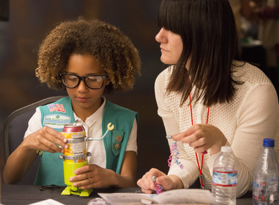"""A Girl Scout builds a soda can robot with help from a female tech executive at the """"She Rules: STEM"""" event at Netflix headquarters in Los Gatos, Calif., Tuesday, Oct. 4, 2016. Girl Scout troops representing Girl Scouts of Northern California met with real-world STEM experts to encourage the pursuit of STEM career paths for young girls."""
