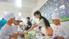 volunteer Jiang Zhaojin instructing students on how to create assorted cold fruit and vegetable dishes