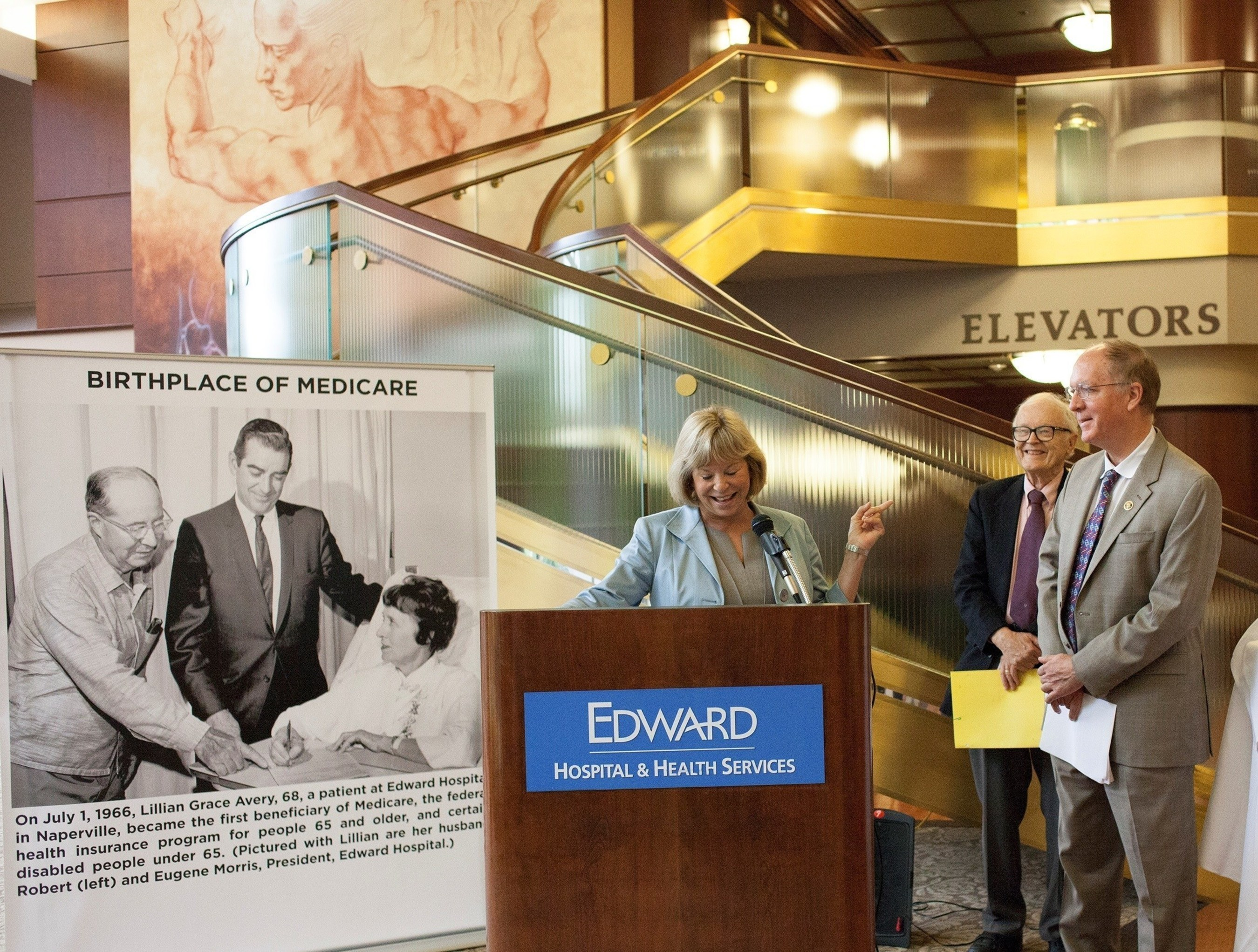 Pam Davis, System CEO, Edward-Elmhurst Health, speaks during a ceremony on July 20 at Edward Hospital in Naperville, Ill. to mark the 50th anniversary of Lillian Grace Avery becoming the nation's first Medicare beneficiary while a patient at Edward on July 1, 1966. With Davis are Rep. Bill Foster (D-Ill.) (far right) and Duane Carlson, who worked for the Blue Cross Association and was involved in Avery's selection as the first beneficiary.