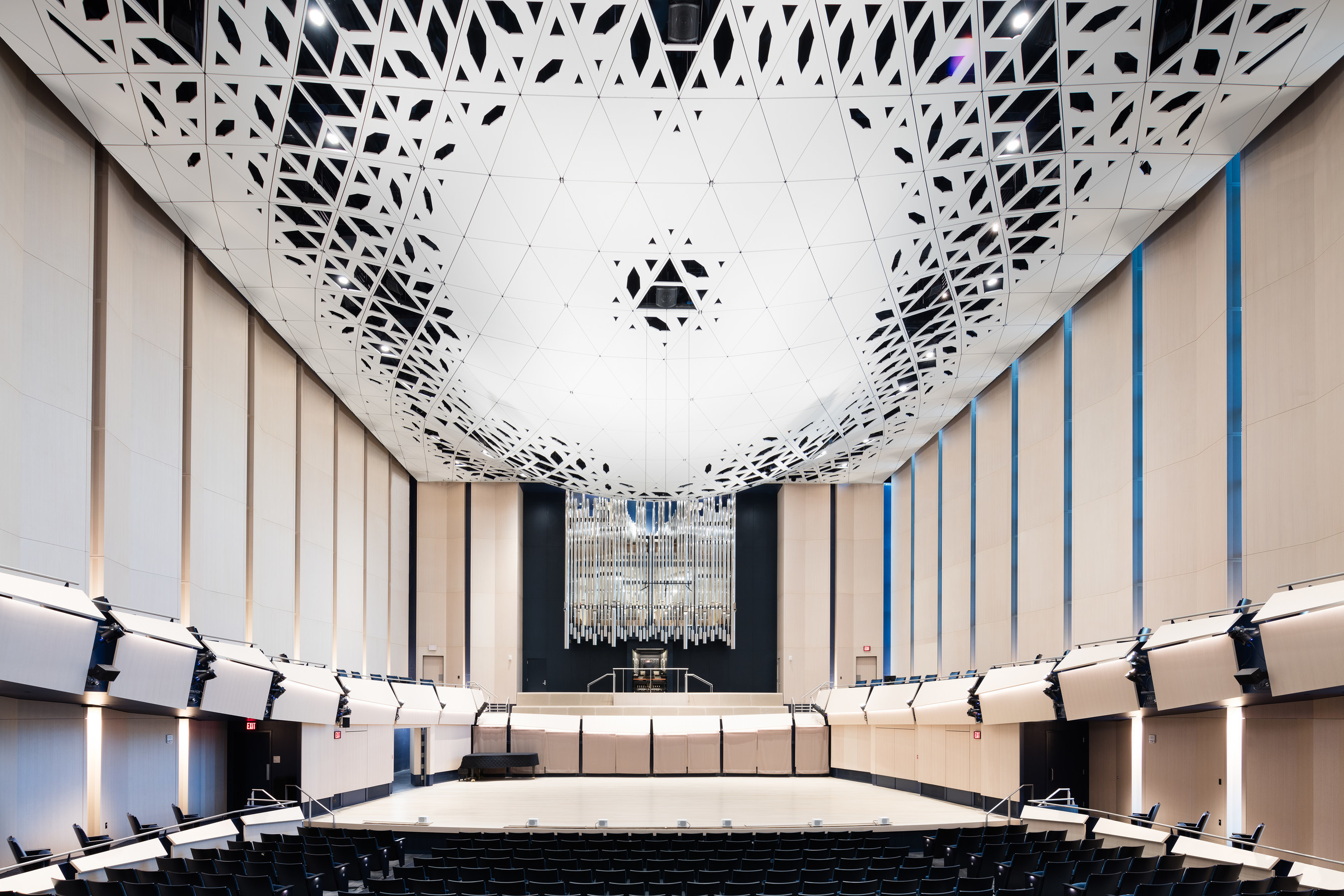 """Voxman Music Building, University of Iowa. The 700-seat performance hall features a """"theatroacoustic"""" ceiling system devised to unify acoustics, lighting, and life-safety requirements into a single dramatic, multi-functional architectural expression. The resulting intricately sculpted element is assembled out of 946 unique, folded-aluminum composite modules. Image courtesy LMN Architects."""