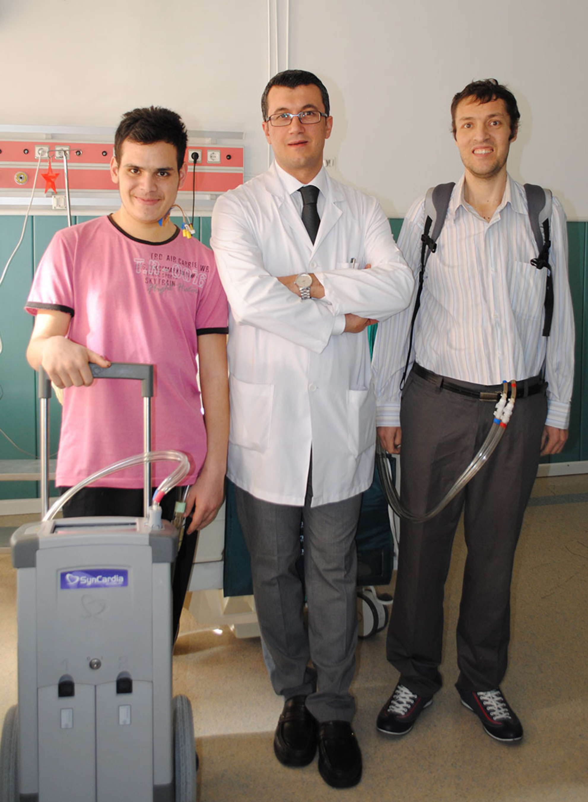 Dr. Umit Kervan, associate professor at Turkiye Yusek Ihstisas Hospital, center, spends time with Turkey's 25th SynCardia Total Artificial Heart implant patient, Sefa Yilmaz, left, who was implanted on Jan. 13, 2014, and Yilmaz Cekic, right, the country's 24th implant patient. Cekic, wearing the Freedom portable driver that powers the SynCardia Heart, was discharged from the hospital on Jan. 31, 2014, less than six weeks after surgeons removed his dying heart and replaced it with the SynCardia Heart.  (PRNewsFoto/SynCardia Systems, Inc.)