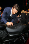 Marvel's Captain America: The Winter Soldier star Chris Evans signs a new Harley-Davidson Street(TM) 750 at the premiere in Hollywood, CA.  Following the premiere, Harley-Davidson will donate the bike to Concord Youth Theatre.  (PRNewsFoto/Harley-Davidson Motor Company)