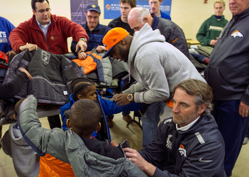 Members of the Knights of Columbus and Denver Broncos distribute free coats to kids at Sacred Heart School in ...