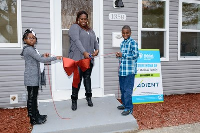 New homeowner Christina Thomas cuts the ribbon in front of her new home, built by global automotive seating supplier Adient through Habitat for Humanity of Huron Valley. Excited to help are her children, Chanel, 7 and Cam'ron, 10.