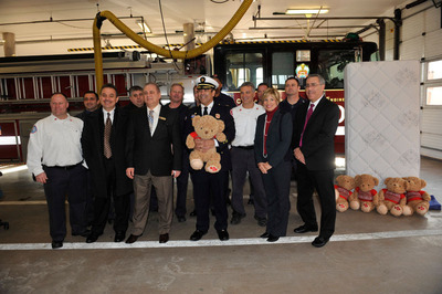 Chicago Fire Commissioner Jose Santiago (center holding an Art Van Furniture Charity Bear) accepts Art Van Furniture's donation of 100 mattresses to the Chicago Fire Department on December 23, 2013 at the Chicago Firehouse Engine 106, Truck 13 and Ambulance 48.  (PRNewsFoto/Art Van Furniture)