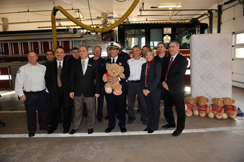 Chicago Fire Commissioner Jose Santiago (center holding an Art Van Furniture Charity Bear) accepts Art Van ...