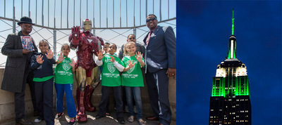 """World-Famous Avenger, Iron Man, joined Police Athletic League (PAL) kids atop the Empire State Building which was lit in green and white on Thursday, May 29 to celebrate PAL's centennial. Joining Iron Man and the PAL kids were JD Michaels (far left, SVP, Director of Tactile Production and Creative Engineering, BBDO NY) and Marcel Braithwaite (far right, PAL Director of Center Operations).  Both were on hand as part of the launch of a new Avengers comic book, """"Heroes Welcome,"""" created by BBDO New York and its Diversity Council and Marvel Custom Solutions.  #PALNY100 (PRNewsFoto/BBDO New York)"""