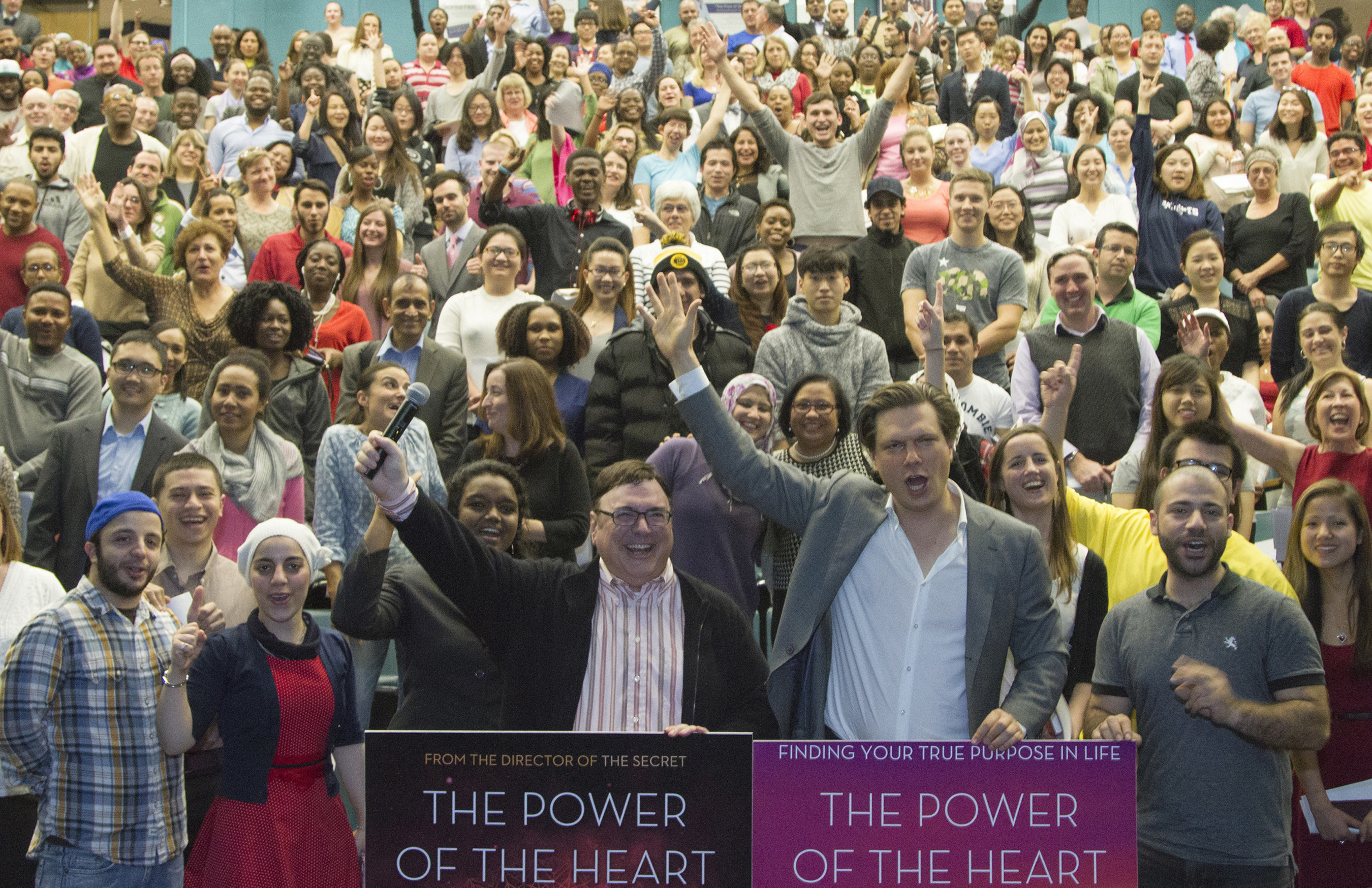 An overflow audience cheers the words of author and filmmaker Baptist de Pape (at right podium) at the presentation of his film The Power of the Heart.