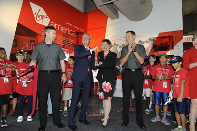 Virgin America COO Steve Forte and Frontiers of Flight Museum President and CEO Cheryl Sutterfield-Jones cutting the ribbon during the  unveiling of the airline's new exhibit at the museum. Virgin America, the airline known or low fares and upscale service, also demonstrated its support for the local community by announcing it will help provide scholarships for students attending the Museum's Flight School and other educational programs.