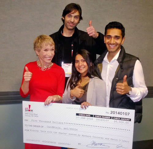 Card Ninja wins Shark Tank-style competition for best promotional product at ASI trade show in Orlando. Company co-founder Sunder Jambunathan, at far right, with Shark Tank judge Barbara Corcoran, in red, and co-presenters Rupa Mohan, center, and Christopher Page, with their winning $5,000 check. (PRNewsFoto/Advertising Specialty Institute) (PRNewsFoto/ADVERTISING SPECIALTY INSTITUTE)