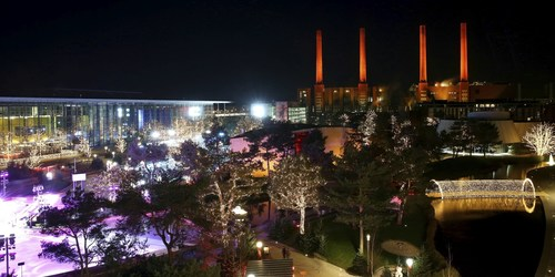 The four smokestacks above the Volkswagen KraftWerk power plant shine festively over the parkland of the ...