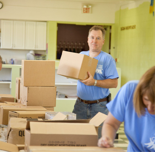 Andre Hawaux, president of Consumer Foods for ConAgra Foods, Inc., helps unpack boxes of donated food to stock ...