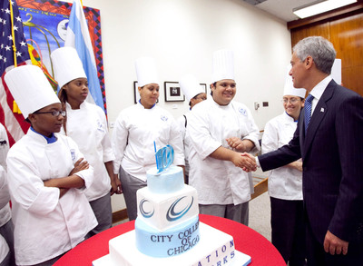 Student chefs from the Washburne Culinary Institute of City Colleges of Chicago present Chicago's Mayor Rahm Emanuel with a cake celebrating the City Colleges of Chicago centennial.