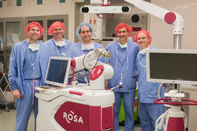 Members of the Premier Health/Medtech team gather after the first U.S. surgery using ROSA Spine. The surgery took place April 21 at Miami Valley Hospital in Dayton, Ohio, which is part of Premier Health. Standing with the ROSA Spine robotic device are, left to right: Scott Wherry; Michael VanWinkle; Juan Torres-Reveron, MD, PhD; Thibaud Partridge; and Eric Heinz. Medtech officials are in red surgical caps, while Dr. Torres-Reveron of Premier Health is in a blue surgical cap.