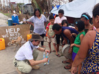 Dr. Eduardo Dolhun demonstrates how to use Drip Drop ORS to survivors of Typhoon Yolanda in Palo, Leyte, Philippines. To find out more visit www.DripDrop.com.  (PRNewsFoto/Drip Drop Inc.)