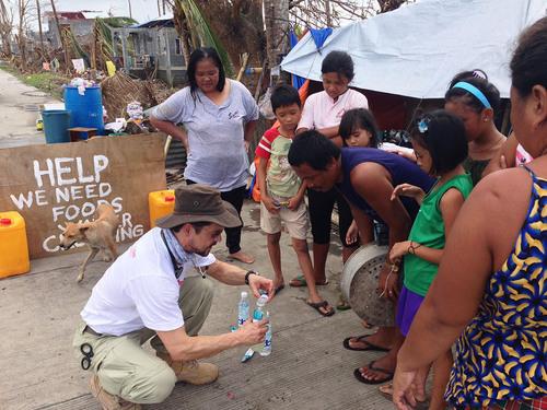 Dr. Eduardo Dolhun demonstrates how to use Drip Drop ORS to survivors of Typhoon Yolanda in Palo, Leyte, Philippines. To find out more visit www.DripDrop.com. (PRNewsFoto/Drip Drop Inc.) (PRNewsFoto/DRIP DROP INC.)