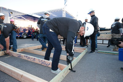 NASCAR Champion Jimmie Johnson and Lowe's Heroes employee volunteers frame a house alongside a local Habitat family at Las Vegas Motor Speedway.