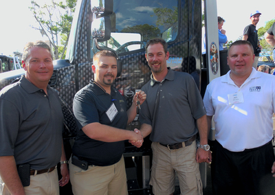 Pictured from left: Vince Tiano, Vice President of Miller Industries; Aaron Forron; Will Miller, President and Co-CEO of Miller Industries; and Gary Mickiewicz, Vice President, Eastern Region of Hino Trucks.