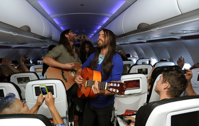 "In this photo released by Virgin America, commercial guests onboard the airline's inaugural flight from San Francisco International Airport to Austin-Bergstrom International Airport live tweeted a live, in-flight acoustic performance at 35,000 feet  by the award-winning Austin-based psychedelic rock band, The Bright Light Social Hour, http://www.thebrightlightsocialhour.com, on May 21, 2013.  En route from SFO to the ""live music capital of the world,"" parts of the unique ""in air"" concert onboard Virgin America were streamed via the airline's fleetwide in-flight WiFi.  (PRNewsFoto/Virgin America)"