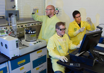 From left, Los Alamos scientists Roy Copping, Sean Reilly, and Daniel Rios. Copping examines the Buchi Multivapor P-12 Evaporator, and Reilly and Rios are at the Agilent Technologies Cary 60 UV-Vis Spectrometer.  (PRNewsFoto/Los Alamos National Laboratory)