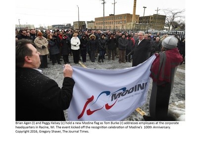 Brian Agen (l) and Peggy Kelsey (c) hold a new Modine flag as Tom Burke (r) addresses employees at the corporate headquarters in Racine, WI. The event kicked off the recognition celebration of Modine's 100th Anniversary. Copyright 2016, Gregory Shaver, The Journal Times.