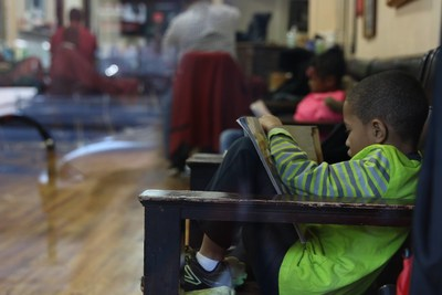 A boy reads while he waits for a haircut.
