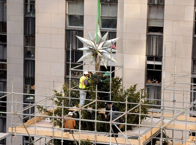The Swarovski Star is placed on top of the 85-foot Rockefeller Center Christmas tree, Thursday, Nov. 13, 2014, in New York. The Star, featuring 25,000 crystals and weighing 550 pounds, will sit atop the Rockefeller Center Christmas tree which will be lit on Dec. 3.