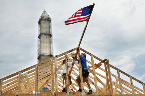 David Burja (right), construction supervisor, and Dave Guttman (left), director of construction, both from Habitat for Humanity Susquehanna, help to raise an American flag over a new Habitat house, during the 2013 Build on the Mall. Veterans, active military and AmeriCorps members are spending this week framing seven houses on the National Mall, to raise awareness about Habitat's Veterans Build and Repair Corps programs.  (PRNewsFoto/Habitat for Humanity International)
