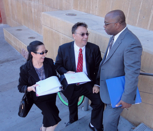 Tony Dane (Center) prepares closing arguments with the help of friend Jeffrey Lewis (Right) and Eviana Conrad ...