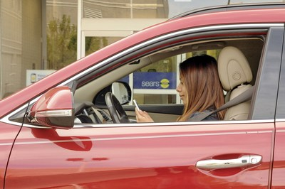 A shopper uses the Sears mobile app, activating its In-Vehicle Pickup service to get her online purchases delivered to her car at the Sears store in Oakbrook, Ill. Retail experts anticipate 2015 will be the most connected holiday ever, with online and in-store shopping experiences becoming more seamless using enhanced mobile features and more integrated retail options.