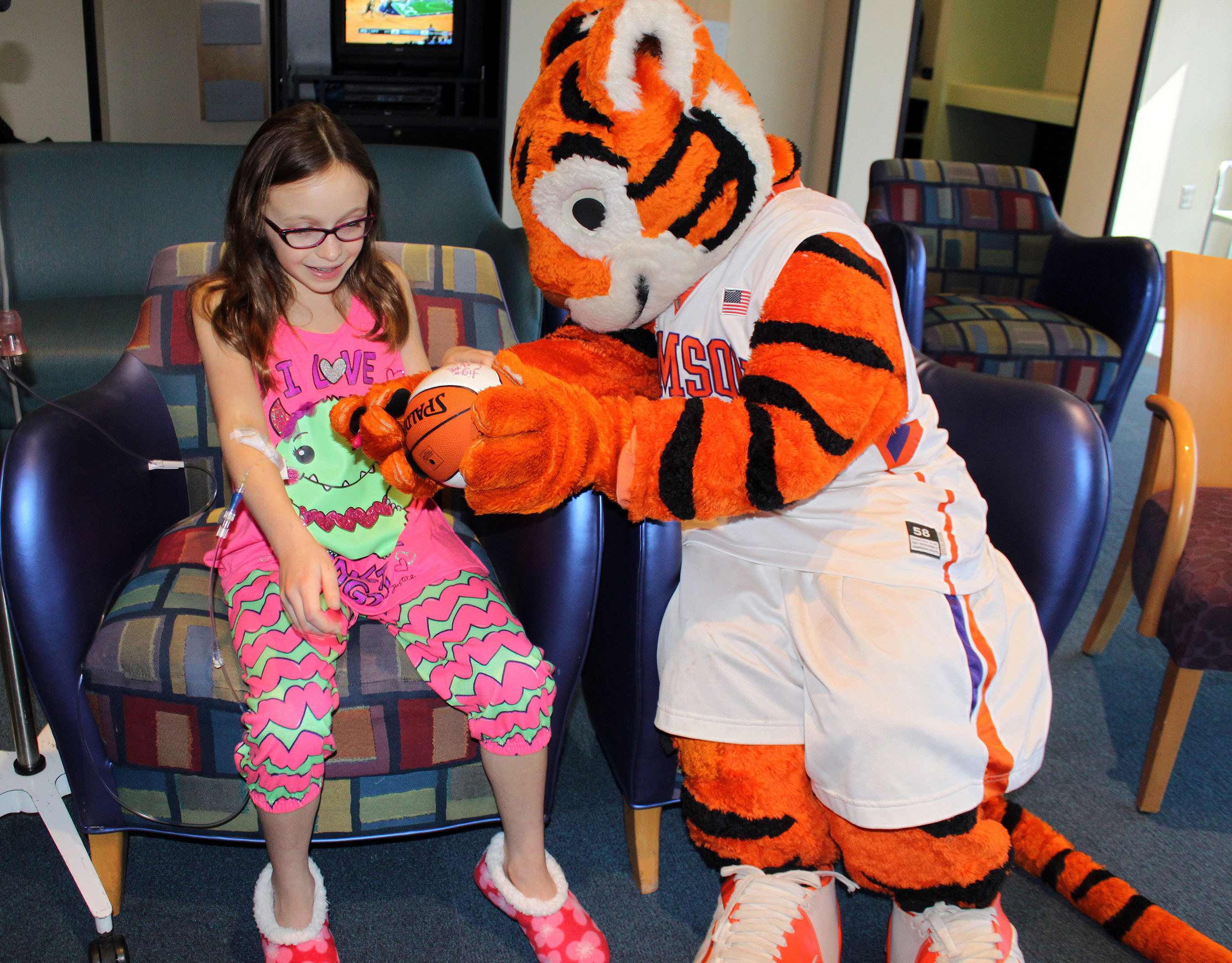 Aspiring actress Emma Miller accepts a signed basketball from the Clemson Tiger Cub. The mascots of the Atlantic Coast Conference paid a visit to Brenner Children's Hospital as part of an outreach initiative for the 2014 ACC Men's Basketball Tournament. (PRNewsFoto/Wake Forest Baptist Medical Center) (PRNewsFoto/WAKE FOREST BAPTIST MEDICAL ...)
