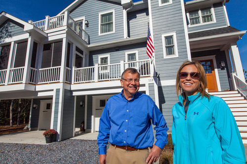 Marnie Homes' President Marnie Oursler, with homeowner Bill Gay outside his American-sourced home in South Bethany Beach, Delaware. Working with 84 Lumber, Ms. Oursler is spreading the word that homes can be built with up to 95% American products and materials for about the same price as using foreign products -- all while creating American jobs in local communities across the country.  (PRNewsFoto/84 Lumber Company)
