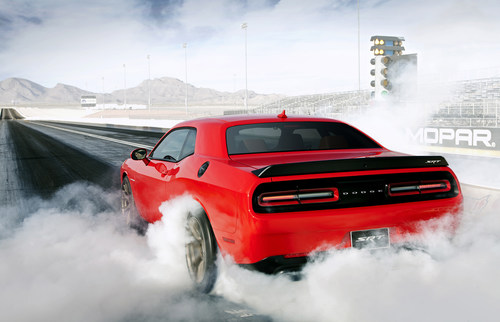 The 2015 Dodge Challenger SRT Hellcat is the fastest muscle car ever with a National Hot Rod Association-certified 1/4-mile elapsed time of 11.2 seconds at 125 miles per hour (mph) with stock Pirelli P275/40ZR20 P Zero tires. With drag radials, the run dropped to just 10.8 seconds at 126 mph!  The Dodge Challenger SRT Hellcat is also the most powerful muscle car ever with an unprecedented 707 horsepower and 650 lb.-ft. of torque. (PRNewsFoto/Chrysler Group LLC)