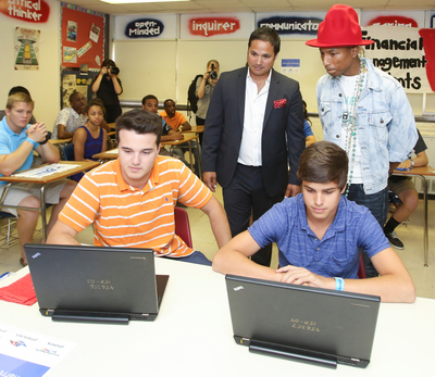 EverFi Co-Founder Ray Martinez and Pharrell Williams observe students as they engage with EverFi's digital learning courses focused on building critical skills such as financial empowerment, digital citizenship, and STEM readiness. (PRNewsFoto/EverFi, Inc., Keith Cephus)
