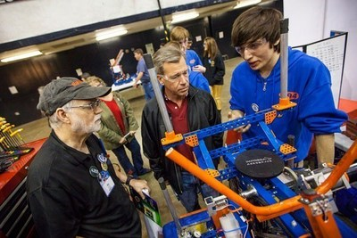 Ric Roberts, left, an engineer at Raytheon Space and Airborne Systems, checks out a student's entry in a robotics competition. Roberts, a longtime supporter of robotics clubs in middle schools and high schools, organizes a Los Angeles-area tournament every year. Standing next to Roberts is Pete Gould, vice president of engineering for Raytheon Space and Airborne Systems.