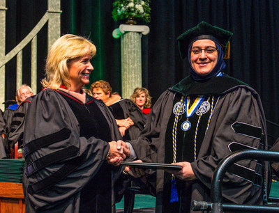 EMU regent Mary Treder Lang congratulates Rula Odai Hashem as she receives her doctorate from the College of Technology at the University's recent commencement ceremony on Dec. 19, 2015.
