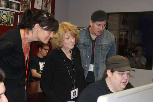 Vanessa Coifman of RKO Pictures, left, Exceptional Minds' Susan Zwerman and director Kyle Newman look on as a very exceptional student, Jeremy Pollock, shows some of his work. (PRNewsFoto/Exceptional Minds)