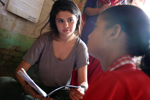 In Nepalgunj, a student shows UNICEF Ambassador, Selena Gomez her schoolwork. As a working adolescent earning additional income for her family, the young girl is happy to receive an education for two hours per day in a UNICEF-supported non-formal classroom setting. Photo Credit: Courtesy of U.S. Fund for UNICEF/Josh Estey/MatiHati (PRNewsFoto/U.S. Fund for UNICEF)