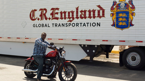 C.R. England has awarded a 2013 Harley-Davidson Sportster Iron 883 to Chris Johnson, one of its top company drivers, for showing improvement in miles per gallon average and average idle percentage for the first quarter 2013. Johnson is pictured with his new Harley.  (PRNewsFoto/C.R. England, Inc.)