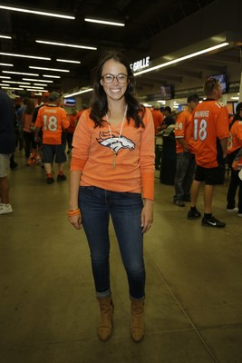 A Denver Broncos fan shows off her personal style, sporting a GIII Touch Essential Goal Line Shirt from the NFL Women's Apparel Collection.