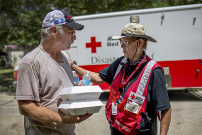 """It's overwhelming,"" says Mike Armstrong, who is beginning to clean up following historic flooding across parts of southern Louisiana, including Denham Springs where Armstrong has lived for more than 30 years. Armstrong welcomed iced water and hot meals from Red Cross volunteer Cora Lee, a local relief worker.Photo by: Marko Kokic/American Red Cross"
