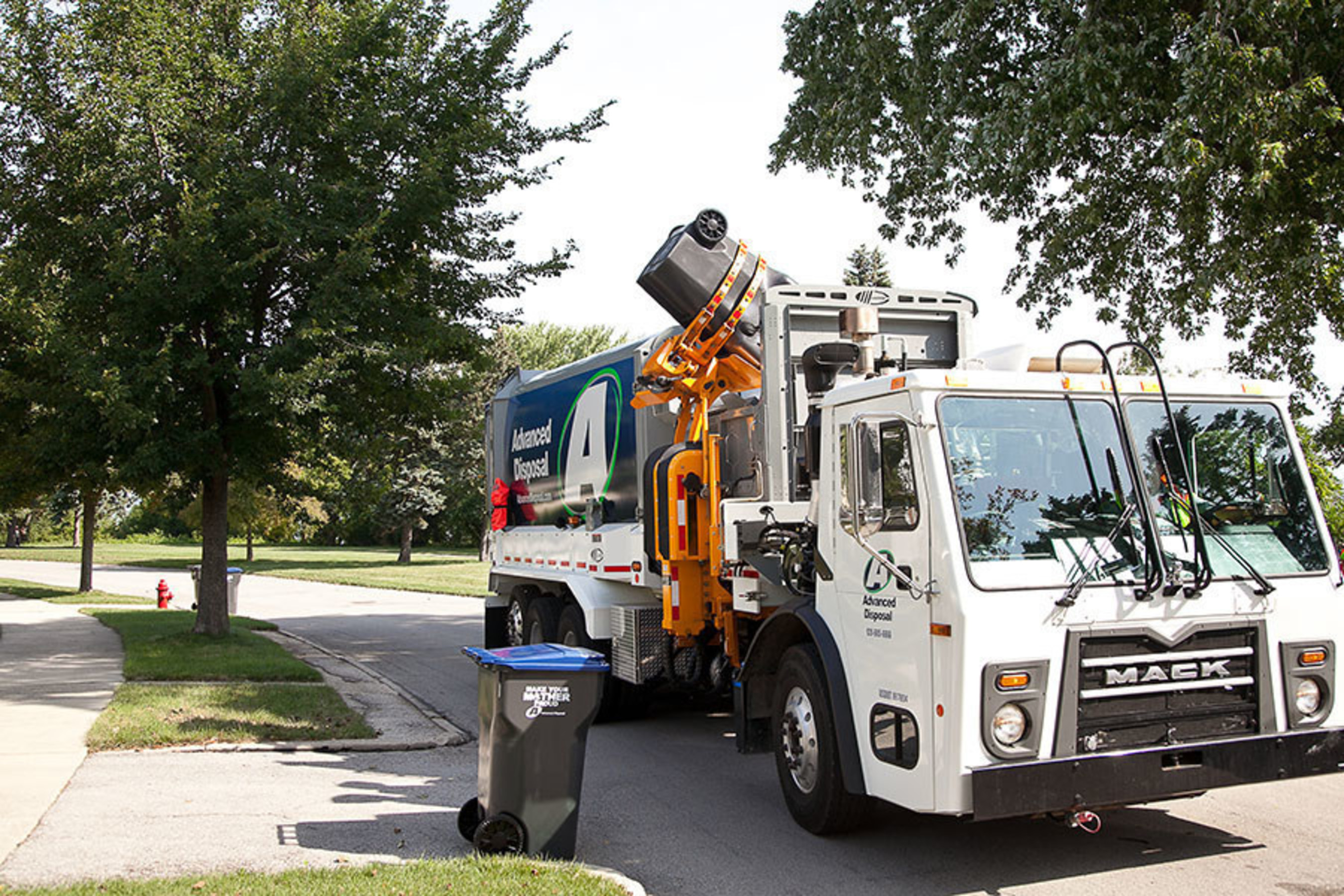 Advanced Disposal automated side-loading truck collecting 96-gallon cart in residential neighborhood.