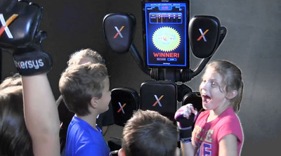 Kids celebrate winning the multiplayer competition round on the Nexersys. The new child's mode allows children 14 years and younger to get into fitness by competing in Avatar Follow Me, Avatar Sparring and Multiplayer Competition rounds.