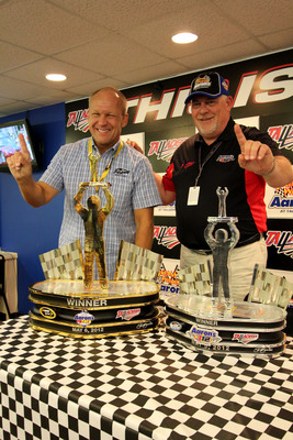 Aaron's, Inc. contracted with renowned motorsports artist Sam Bass (left), to present one-of-a-kind, hand-painted Sam Bass trophies to the winners of the NASCAR Sprint Cup Series Aaron's 499 and Nationwide Series Aaron's 312 at Talladega Superspeedway May 5 and 6.  Bass showcased the trophies at a press conference on Saturday, May 5, with Aaron's COO Ken Butler (right). Each trophy will feature an image of the driver standing atop a custom painting of the winning car.  (PRNewsFoto/Aaron's, Inc.)